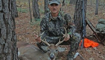 hunter in camo holding a dead deer's antlers