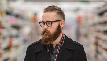a hipster with a beard and glasses in a supermarket aisle