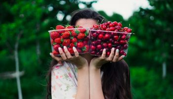 a woman holding two plastic containers of strawberries and cherries in front of her face