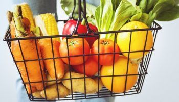 a shopping basket full of fresh fruit and vegetables