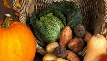 pumpkin and vegetables near a wooden basket