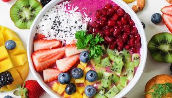 a breakfast bowl of fruit and smoothies surrounded by more fruit