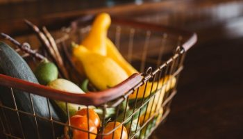 a shopping basket with fruits and vegetables in it