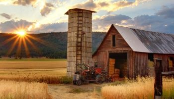 a barn and a tractor in the countryside