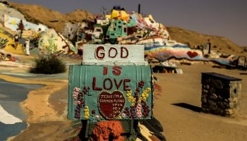 "a sign that says ""God is Love"" in a desert"
