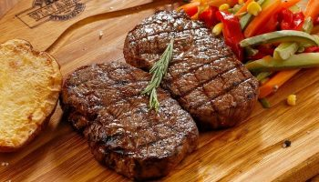 steak and vegetables on a wooden cutting board
