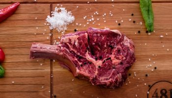 raw meat with salt on a wooden cutting board next to a steak knife