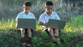 two Taiwanese kids on laptops in nature