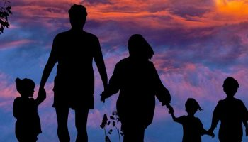 the silhouette of a family with a scenic backdrop of the sky
