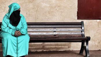 a Muslim woman sitting on a bench