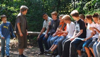 a large group of teenagers sitting together in the woods