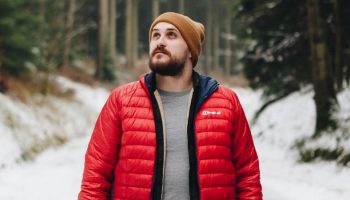a man with a beanie in a snowy forest