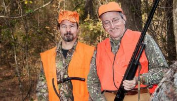 two hunters with high visibility vests and hunting rifles