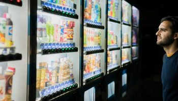 a man deciding what to buy in front of a row of vending machines