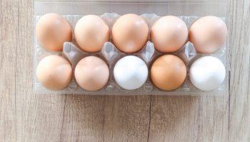a carton of ten eggs on a wooden board