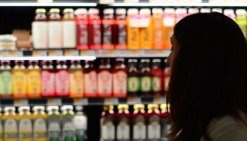 a woman shopping in the juice aisle