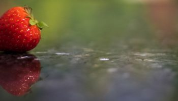 a strawberry on a reflective surface