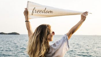"""a woman holding a triangular sign saying """"freedom"""""""