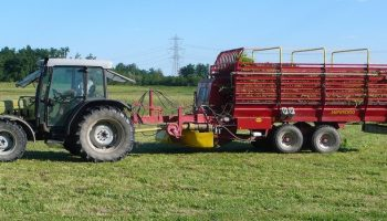 tractor pulling along a large carriage of cut grass