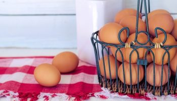 brown eggs in a basket on a red tablecloth