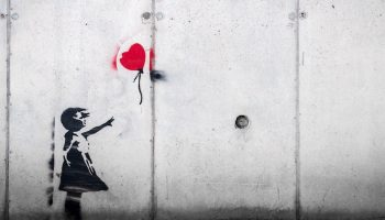 a graffiti picture of a girl with a red balloon escaping her hand