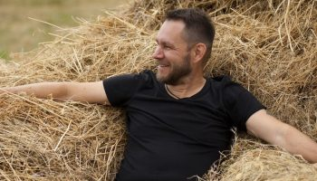 a man sitting in hay