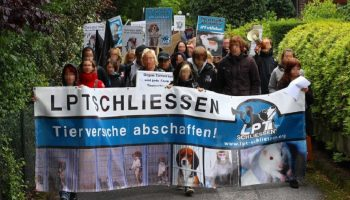 animal activist march through the streets with a banner decrying animal experimentation