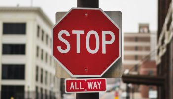 """a red pedestrian sign that says """"stop"""""""