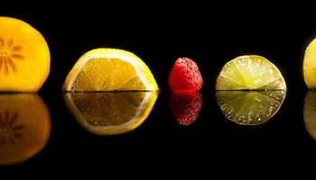 five pieces of different fruit with a black background