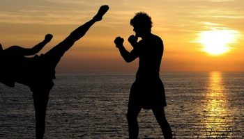silhouette of a man and woman kick boxing