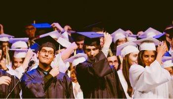 university graduates throwing their hats off
