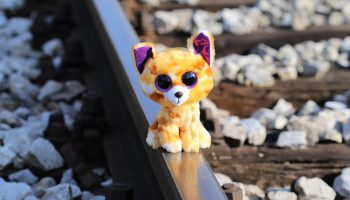 a toy cat on a railroad track