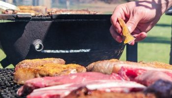 man putting sauce on a meat barbecue