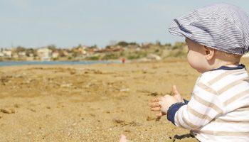a preschooler playing on a sandy beach