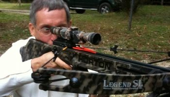 a hunting holding a camouflaged crossbow