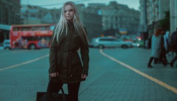 a blonde woman standing on a British street holding a bag