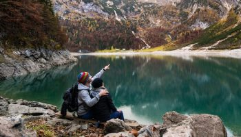 a man and a woman sitting near a large lake