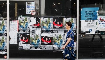 woman walking past posters on wall