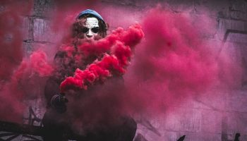 a masked man holding a red smoke canister with smoke enveloping him