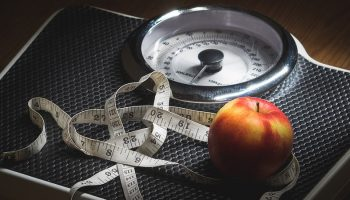 weighing scale, with an apple and measuring tape on it
