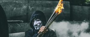 a man wearing an anonymous mask whilst holding a bundle of sticks on fire