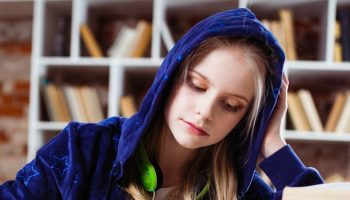 a female student studying with a hoodie on