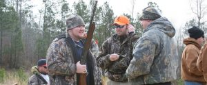 hunters standing together in circles holding rifles