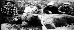 old photo of a dead bear surrounded by hunters who shot it