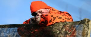 hunter in high visibility coat aiming a rifle