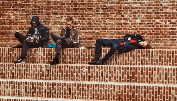 three young adults sitting on brick steps
