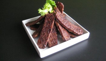slices of tempeh bacon artfully arranged and garnished on a square white plate
