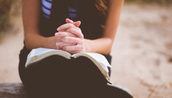 woman with hands clasped in prayer over an open bible