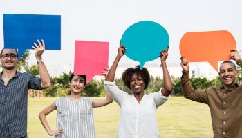 diverse group of people holding up word bubbles in a field