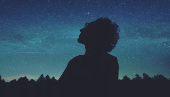 silhouette of a person staring at the stars in the night sky